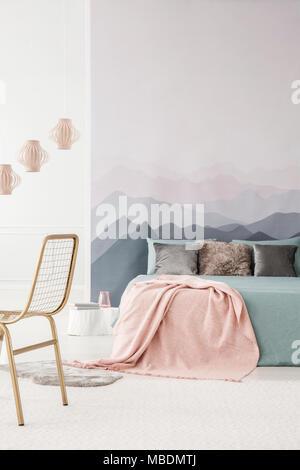 Rosa Decke auf grau Bett im gemütlichen Schlafzimmer Innenraum mit Lampen und gold Stuhl - Stockfoto