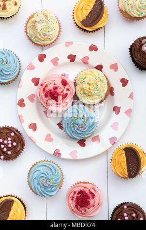 Bunten Cupcakes auf einem herz-muster Platte Muster
