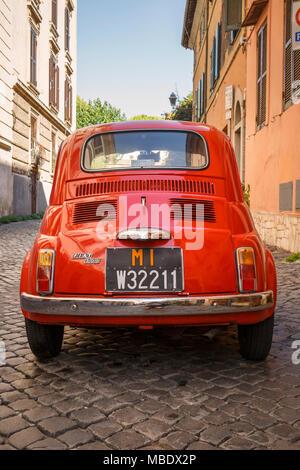 Rückansicht eines alten roten Fiat 500 in einer gepflasterten Straße in Rom, Italien, außerhalb eines Gebäudes unter italienischer Flagge geparkt. Die nummernschilder ein MI pr anzeigen - Stockfoto