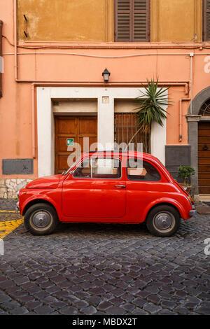 Ein alter roter Fiat 500 in einer gepflasterten Straße in Rom, Italien, außerhalb eines Gebäudes geparkt, das Werk ist nicht aus dem Schiebedach! - Stockfoto
