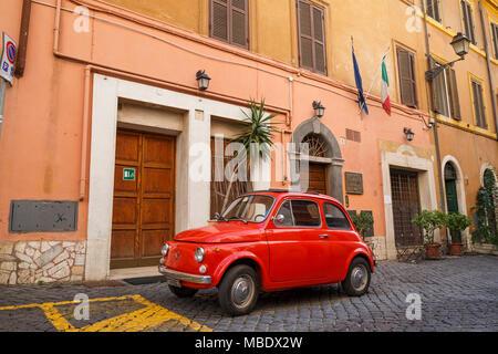 Iconic Ansicht einer alten roten Fiat 500 in einer gepflasterten Straße in Rom, Italien, geparkt, außerhalb eines Gebäudes unter italienischer Flagge. Die Nummernschilder zeigen ein MI - Stockfoto