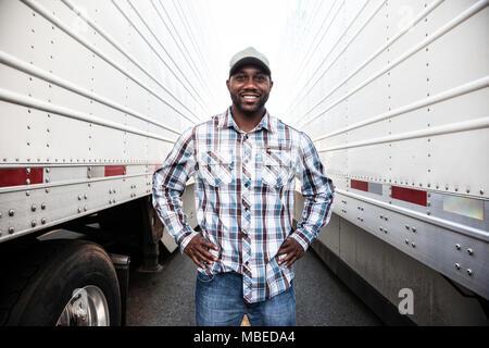 Ein LKW-Fahrer stehen zwischen zwei großen LKW-Anhänger in einem trailer park, die Hände auf den Hüften, lächelnd, Arbeitskleidung - Stockfoto