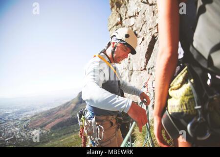 Kletterausrüstung Englisch : Frau kletterer binden seil im knoten und vorbereitung zu klettern