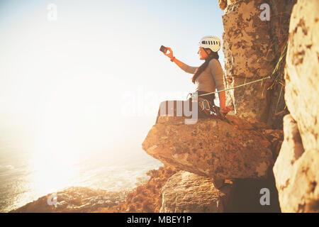 Weibliche Kletterer mit Kamera Handy fotografieren Sunny ocean view - Stockfoto