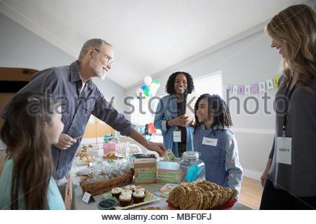 Mann kaufen Desserts von Mädchen an backen Verkauf im Community Center - Stockfoto