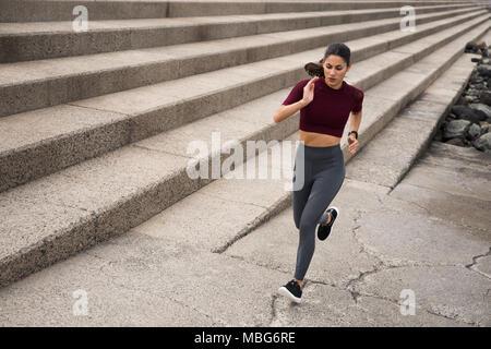 Sportliche junge Frau, die auf Treppen in Fitness Kleidung mit Haaren gebunden zurück