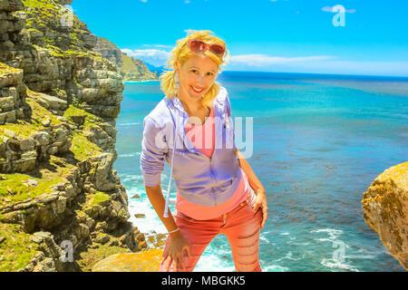 Südafrika Urlaub Konzept. Happy kaukasische Frau am Cape Point Kap, der südöstlichen Ecke der Kap Halbinsel. Weibliche Touristen genießen am Kap der Guten Hoffnung Teil des Table Mountain NP. Blue Sky. - Stockfoto