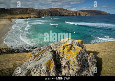 Big Rock in leuchtend gelben Flechten mit Blick auf Surf Beach mit tropischen Blick auf das Meer auf der Insel Lewis, Schottland abgedeckt. - Stockfoto