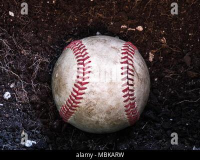 Close up Sport Hintergrund Bild eines alten verwitterten Leder baseball Verlegung in einem Haufen von braunen Schmutz mit komplizierten Details und roten Schnürsenkeln. - Stockfoto