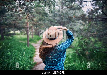 Junge Frau in braunen Hut und Grünen kariertes Hemd mit langen Haaren stehen auf dem harten Wind unter Kiefer in den Wald - Stockfoto