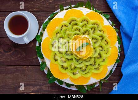 Helle runde festliche Obstkuchen mit Kiwi, Orange, Minze und einer Tasse Tee dekoriert. - Stockfoto