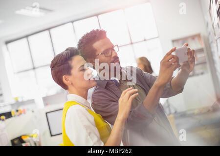 Fokussierten Creative Business Menschen mit Kamera Handy im Büro - Stockfoto
