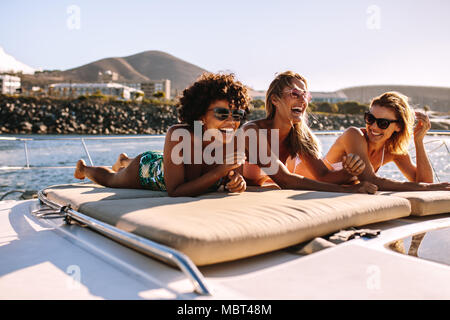 Schöne junge Frauen entspannen Sie sich auf einer privaten Yacht Deck im Meer. Drei weibliche Freunde Sonnenbaden auf luxusyacht und haben eine tolle Zeit. - Stockfoto