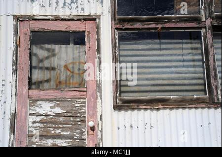 Ein verlassenes Gebäude aus Holz und Wellblech sitzt in einem Zustand des Verfalls. - Stockfoto