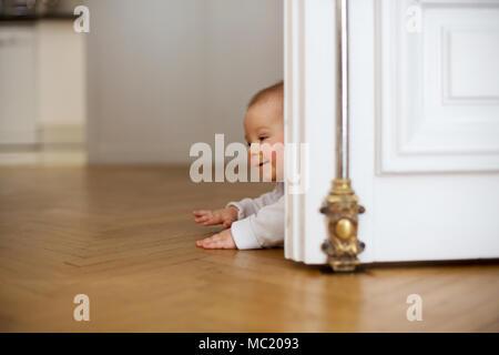 Kleines Baby, Kleinkind, in einem langen Flur, Krabbeln auf dem Boden und lächelt - Stockfoto