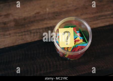Bunte Papier mit Fragezeichen in einem Kunststoffbehälter auf hölzernen Tisch. Fragen und Diversity Konzept. FAQ und Q&A Hintergrund Konzept - Stockfoto