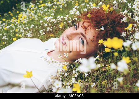 Junge schöne Frau ruht in einem Feld von Blumen - Stockfoto