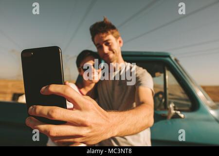 Paar genießen Sie eine Reise in das Land. Paar posieren für ein selfie während jeder andere Holding. - Stockfoto