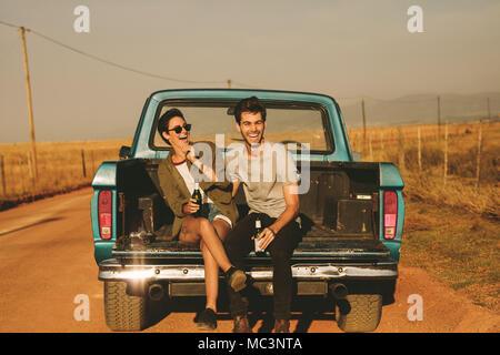 Lächelndes Paar in der Rückseite ihres Pickup Truck sitzen, genießen die Straße Reise im Land. Mann und Frau mit einer Flasche trinken genießen die - Stockfoto
