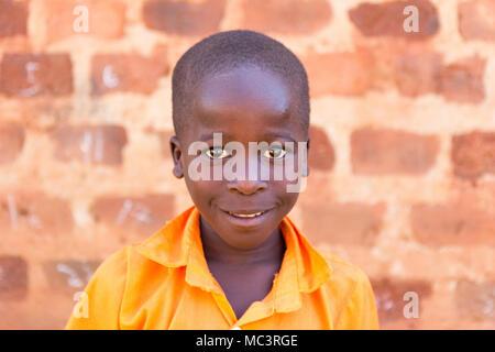 Uganda. 13. Juni 2017. Ein lächelndes ugandischen Junge in einem orangefarbenen Uniform an der Grundschule. - Stockfoto