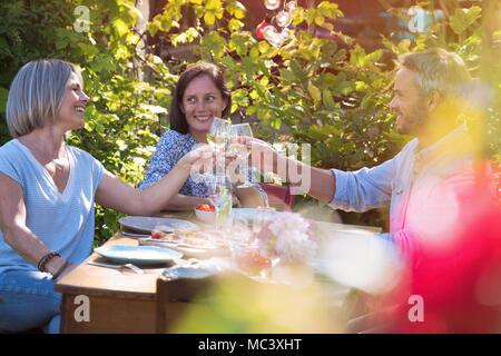 Im Sommer, eine Gruppe von Freunden in den Vierzigern versammeln sich um einen Tisch im Garten eine gute Zeit, um eine Mahlzeit zu teilen. Stockfoto
