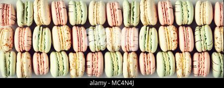 Bunte französische Makronen flach. Pastellfarben Pink, Grün, Gelb macarons mit Kopie Raum, Ansicht von oben. Feiertage und Feste Konzept. Süßes Geschenk für Frau, Mädchen. Banner - Stockfoto