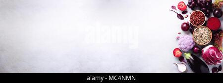 Lila Gemüse, Obst auf grauem Hintergrund. Violett Aubergine, Rüben, Blumenkohl, lila Bohnen, Zwetschgen, Zwiebel, Traube, Quinoa, Reis. Zutaten zum Kochen, Kopieren, Ansicht von oben, flach. Banner - Stockfoto