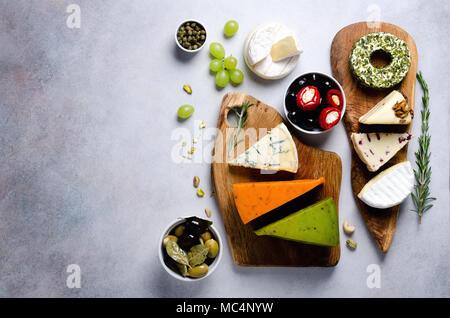 Sortiment an Hart- und Weichkäse mit Oliven, grissini Brot Sticks, Kapern, Traube, auf grauem Beton Hintergrund. Top Anzeigen, Kopieren, flach. Käse Auswahl Aperitif-platte. - Stockfoto