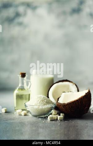 Kokosnüsse Produkte - Milch, Öl, Späne auf grauem Beton Hintergrund. Kopieren Sie Platz. Haar, Haut und Körper Behandlung. - Stockfoto