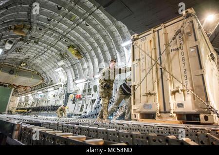 Us Air Force Senior Airman Connor Schuhmacher, ein lademeister der Expeditionary 816th Airlift Squadron zugewiesen wird, hilft ein Container auf einem K Push-Lader von der Flugzeuge am Flughafen Bagram, Jan. 25, 2018. Die C-17 transportiert Truppen und Ausrüstung, Standorte im gesamten US Central Command der Verantwortung zur Unterstützung der Operation, die die Freiheit des Sentinel und der entschlossenen Unterstützung der NATO-Missionen. Der C-17 ist nicht nur tüchtig in den Transport von Truppen und Cargo, aber können taktischer Lufttransport und airdrop Missionen durchführen und den Transport der ambulanten Patienten während der aeromedical Evacuation - Stockfoto
