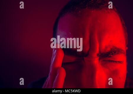 Der Mensch leidet in Schmerz von Kopfschmerzen. Nahaufnahme, Porträt Porträt des Menschen Gefühl umgekippt oder Schmerzen. Er berührt den Kopf mit der Hand. - Stockfoto