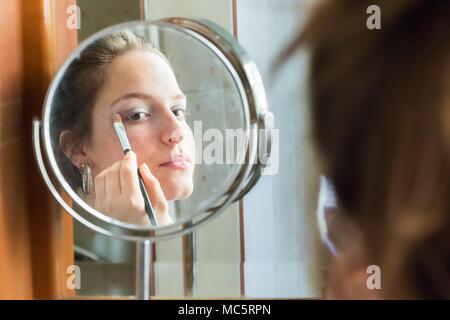 Jugendlicher Mädchen Anwendung Lidschatten ihr Spiegelbild auf einem runden Spiegel zu Hause suchen - Stockfoto