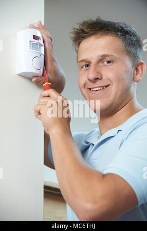 Portrait von Sicherheitsberater Einbau Alarmanlage Sensor im Zimmer - Stockfoto