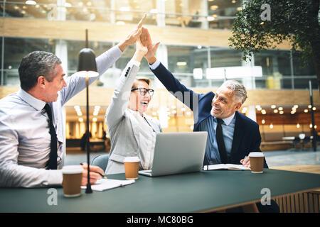 Gruppe von reifen Geschäftsleute hohe einander fiving während einer Sitzung gemeinsam an einem Tisch in der Lobby eines modernen Bürogebäudes - Stockfoto