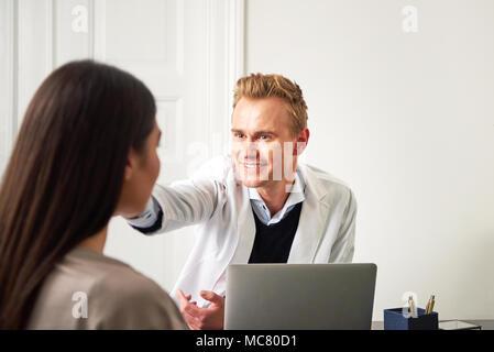 Professionellen Kosmetikerin Mann am Laptop im Büro zu sitzen und das Berühren Frau Gesicht, während Ihr Consulting. - Stockfoto
