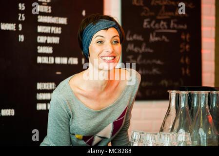 Frau fröhlich lächelnd in Restaurant, Porträt - Stockfoto