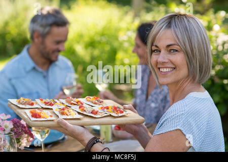 Im Sommer. Eine Gruppe von Freunden um einen Tisch im Garten versammelt, um eine Mahlzeit zu teilen. Eine schöne Frau serviert Ihnen Snacks auf einer Schüssel beim Betrachten - Stockfoto