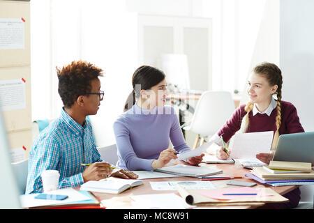 Zwei Mädchen und Kerl saß in der Bibliothek nach dem Unterricht und Vorbereitung der Essay - Lesen und Diskutieren Informationsquellen - Stockfoto