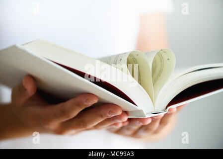 Buchen Sie mit geöffneten Seiten und die Form des Herzens in Mädchen Hände. Kopieren Sie Platz. Liebe Konzept - Stockfoto