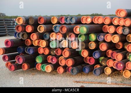 Bohren Rohr mit farbigen Endkappen sitzen in einem Yard off Highway 16 in der Nähe der Ölfelder im Eagle Ford shale Play in McMullin County gestapelt, südlich von San Antonio, Texas. - Stockfoto