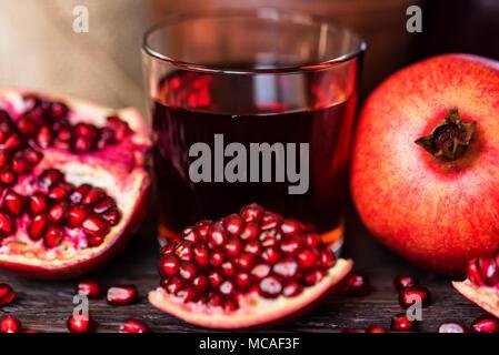 Reife Granatäpfel mit Glas Saft auf dem Tisch - Stockfoto