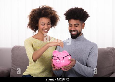 Glückliches Paar sitzt auf einem Sofa einfügen Münze in Sparschwein - Stockfoto