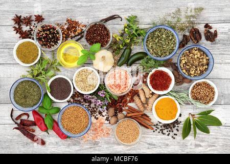 Gewürze und Kräuter würzen mit frischen und getrockneten Kräutern und Gewürzen mit Olivenöl auf rustikalem Holz Hintergrund. Ansicht von oben. - Stockfoto