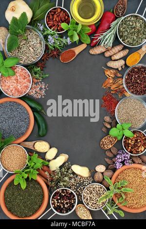 Kraut und Gewürz abstrakt hintergrund Grenze mit frischen und getrockneten Kräutern und Gewürzen mit Olivenöl auf Schiefer. Ansicht von oben. - Stockfoto