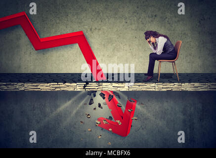 Deprimiert Geschäftsfrau, die an der fallenden roten Pfeil durch einen Betonboden. Herbst und Abschreibungen Konzept. - Stockfoto