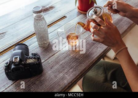 Nahaufnahme einer Frau gießen Kaffee in eine Tasse aus einer Teekanne aus Glas. Frau die Zubereitung von Tee, während eine professionelle Kamera und eine Flasche mit Saft gefüllt sind - Stockfoto