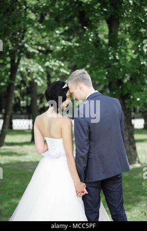 Braut und Bräutigam auf einem Spaziergang im Park