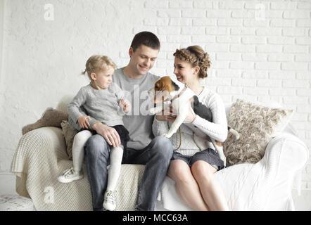 Eltern mit einer kleinen Tochter und pet das Sitzen auf der Couch. - Stockfoto