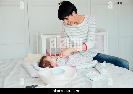 Baby hat ihre Windel von ihrer Mutter auf dem Doppelbett hatte. Die Mutter zur Befestigung der Baby wächst, während verspielt wird. - Stockfoto