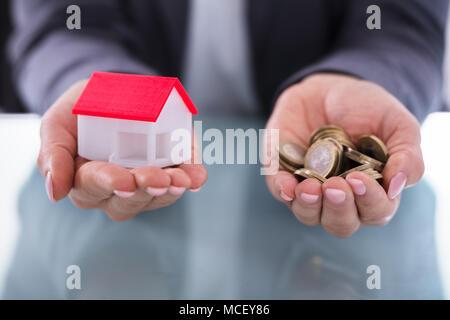 Nahaufnahme der Kaufmann Hand Münzen und Haus Modell - Stockfoto